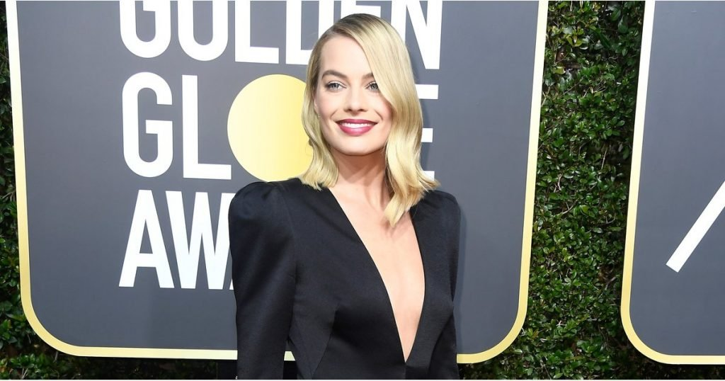 7d4502a5465 Margot Robbie stunned on the 2018 Golden Globes red carpet. The actress  attended the event wearing a long-sleeved black gown that featured a  plunging ...