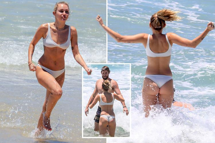 Miley Cyrus flashes her bum in a thong bikini as she splashes around in the sea with fiance Liam Hemsworth