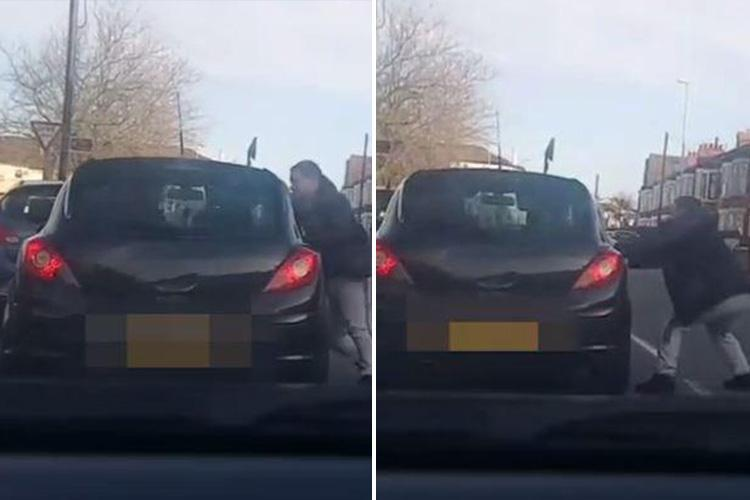Shocking moment pedestrian sprints up to car and viciously punches driver through window