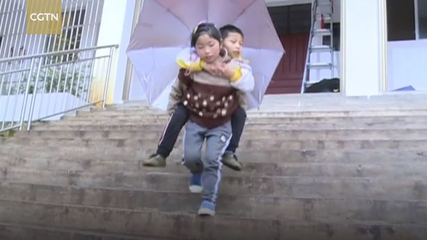 Heartwarming bond between girl, 9, and disabled brother who she carries to school every day