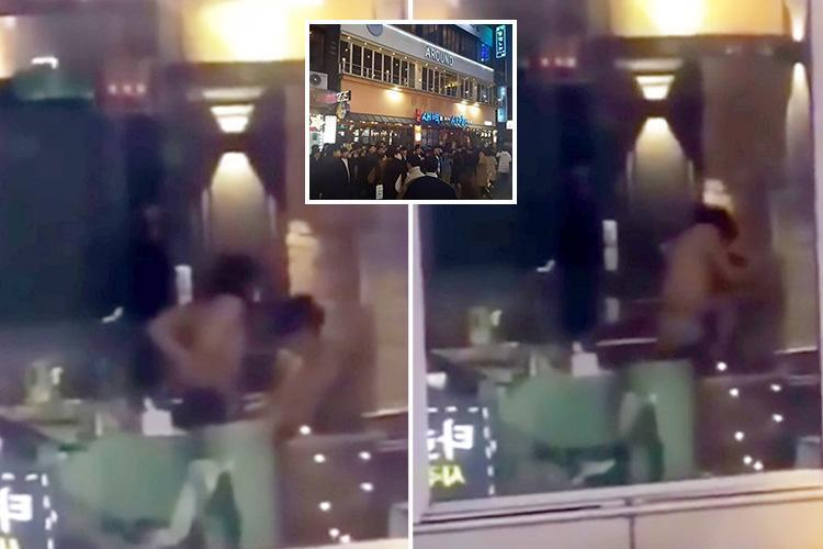 Randy couple romp in hotel room 'completely unaware' that a huge cheering crowd is watching outside… with some even climbing up the building