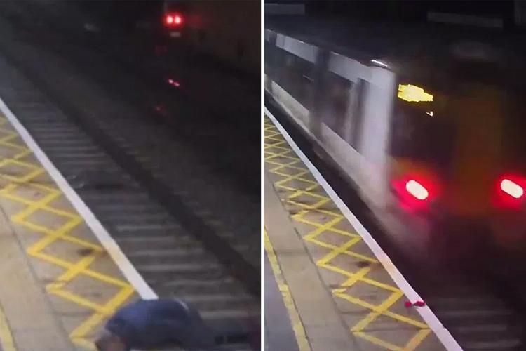 Heart-stopping moment boozed-up reveller risks death by lying down on railway tracks as a train hurtles over him in Harlow
