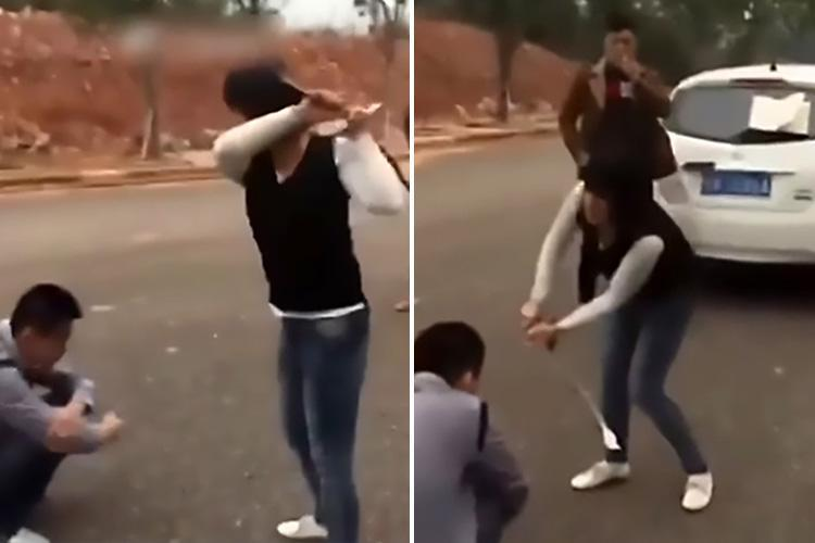 Angry woman attacks her 'cheating' husband with a massive stick as he's forced to cower in the middle of the road