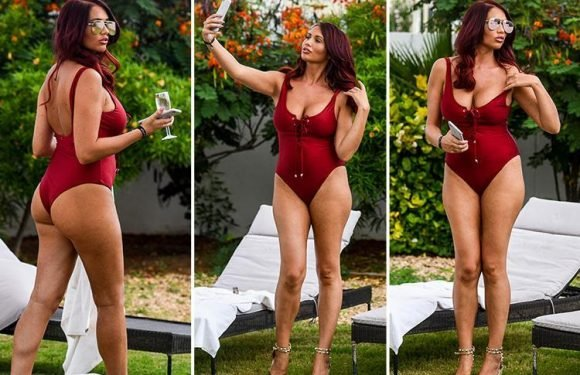 Amy Childs shows off her stunning figure in plunging red swimsuit as she soaks up the sun in Cape Verde