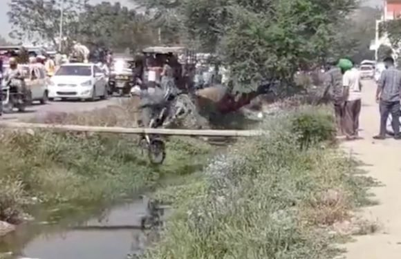 Biker falls into open sewer while trying to cross on narrow wooden plank