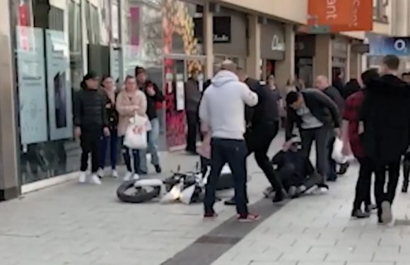 Furious dad drags motorbiker off as he rides through packed shopping street