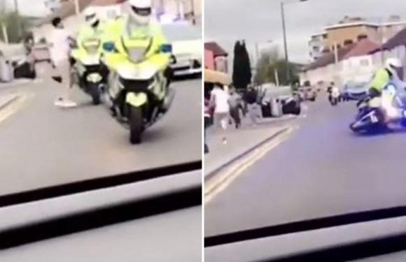Thug shoves cop off his motorbike and into the path of police car before fleeing the broad daylight attack