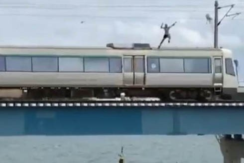Train surfer narrowly avoids death during bridge jump