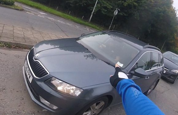 Driver is caught eating at the wheel after cyclist catches him up