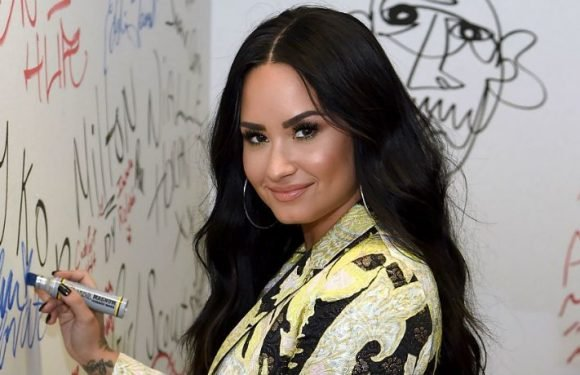 Demi Lovato Poses In Low Cut Swimsuit As She Shares Her New Charity Sunglass Collab