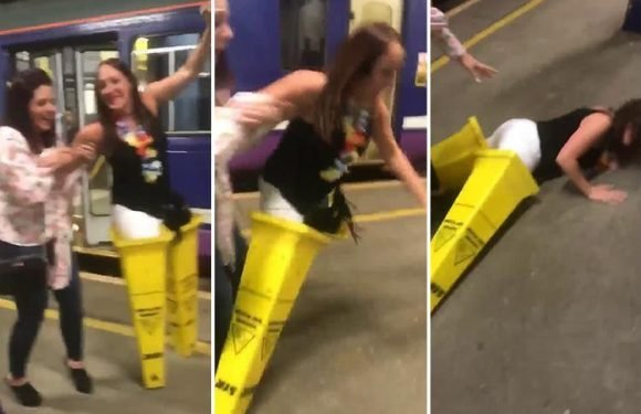 Hilarious moment reveller falls flat on her face after trying to walk down train platform using two giant cones