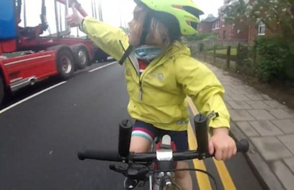 Cyclist Rhoda Jones, 4, gives a thumb-up as lorry overtakes her