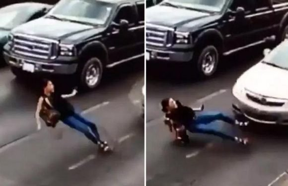 Shocking moment a woman running across a busy road in high heels with her phone in her hand slips and is hit by a car
