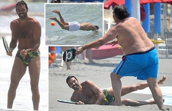 Gianluigi Buffon squeezes into a pair of budgie smugglers as he plays bat and ball with a pal on the beach