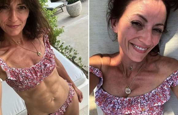 Davina McCall shows off her toned abs in a floral bikini as she relaxes in the sunshine