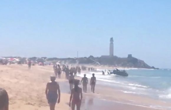 Stunned tourists look on as dozens of migrants land on packed Spanish beach