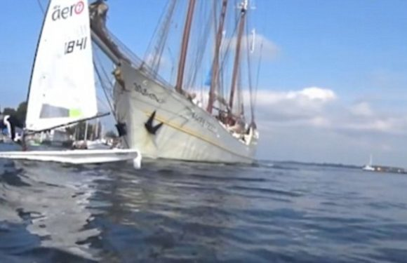 Moment sailor struggles to steer his dinghy out of path of a tall ship