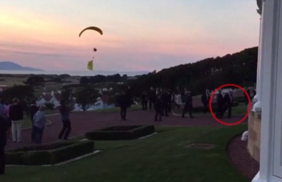 Trump quickly ushered away as protesting paraglider buzzes above him