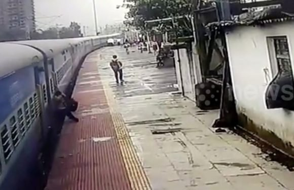 Man trying to board train gets dragged along platform before being saved by cop