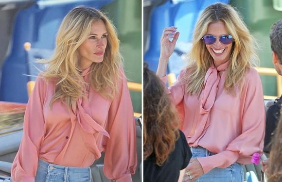 Julie Roberts wows in pussybow pink blouse and fitted jeans as she leans against Mercedes