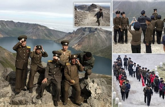 North Koreans in military outfits scale the Mount Paektu volcano