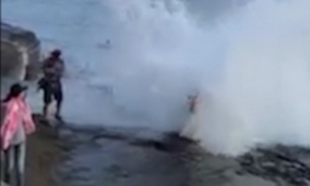Newlyweds get soaked by huge wave during beach photoshoot