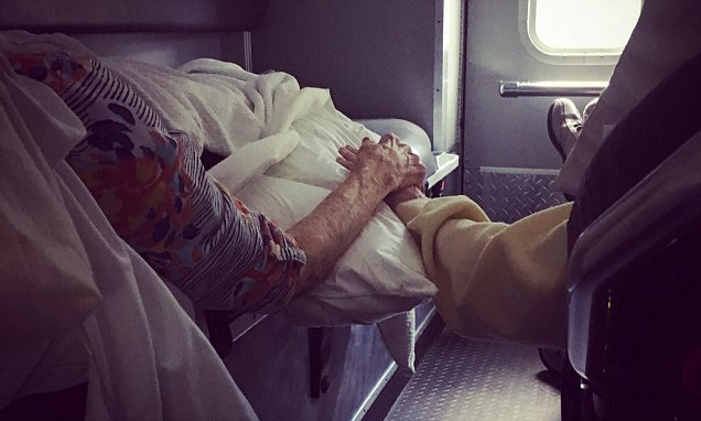 Elderly couple fleeing Florence hold hands in the back of ambulance