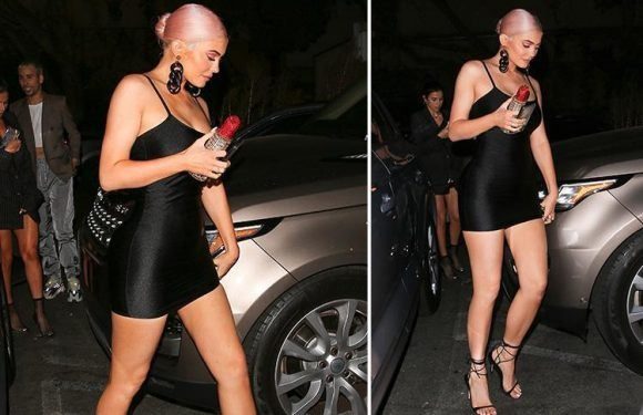 Kylie Jenner shows off new pink hair as she wears a black mini-dress and carries sparkly lipstick clutch bag for night out in LA