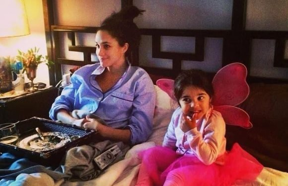 Rare makeup-free snap of Meghan Markle shows her snuggling up to goddaughter in bed while watching TV
