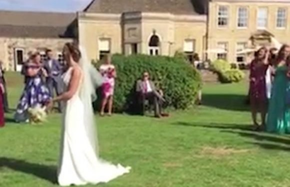 Man has a VERY dramatic reaction after his girlfriend catches the bouquet at a friend's wedding
