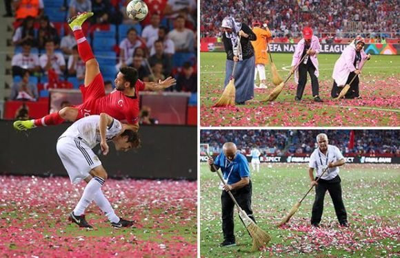 Workers clear ticker tape off Turkey pitch with old brooms as grass is covered during Russia clash
