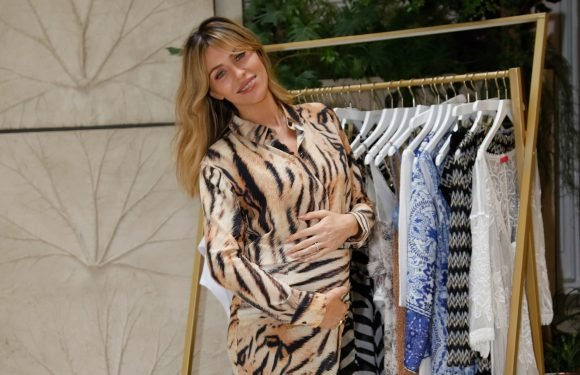 Abbey Clancy caresses her baby bump in a tiger print dress at the launch of her new Lipsy collection