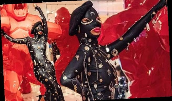 Cardi B puts on a VERY racy display in a rubber dress and mask