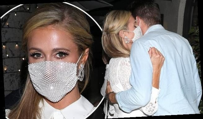 Paris Hilton wears pretty white lace prom-style dress and face mask