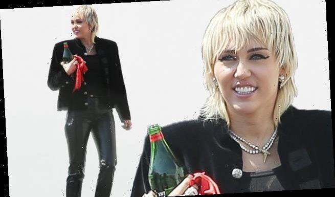 Miley Cyrus works flashy PVC trousers and a military style coat