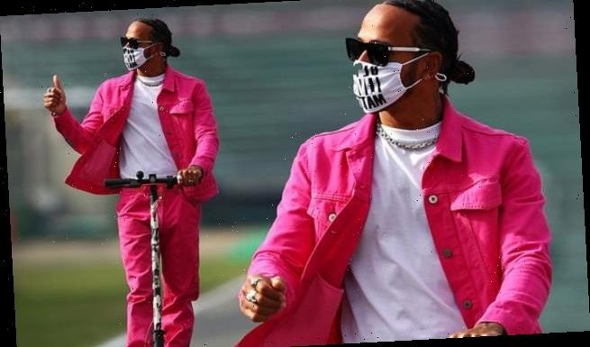 Lewis Hamilton raises the style stakes in a pink jacket and jeans