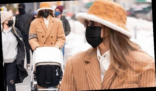 Gigi Hadid models a tan trench-style winter coat and Louis Vuitton hat