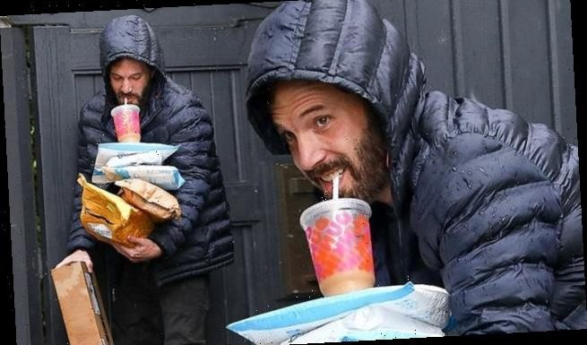 Ben Affleck juggles packages and Dunkin Donuts iced coffee in rainy LA