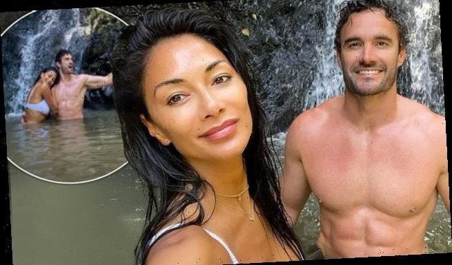 Nicole Scherzinger and beau Thom Evans pose beside waterfall in Hawaii