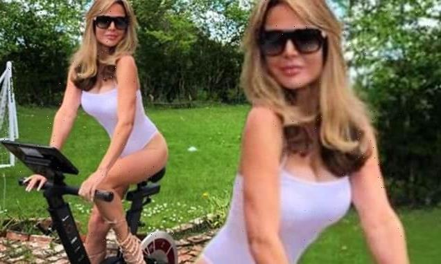 Lizzie Cundy hops onto exercise bike wearing leotard and heels