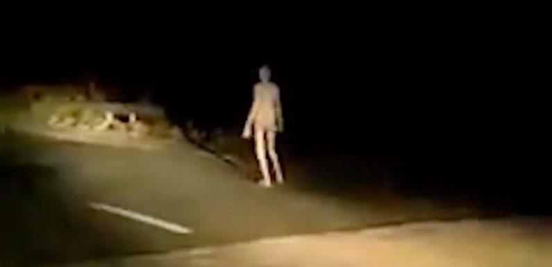 Creepy 'alien' figure with long limbs walks along bridge at dead of night