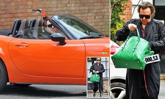 Jonathan Ross rummages through his £2,000 green Gucci leather handbag