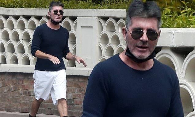 Simon Cowell shows off his slim figure in a blue top and white shorts