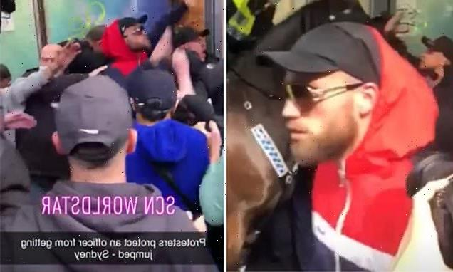 Moment anti-lockdown protesters protect a police officer from rioters