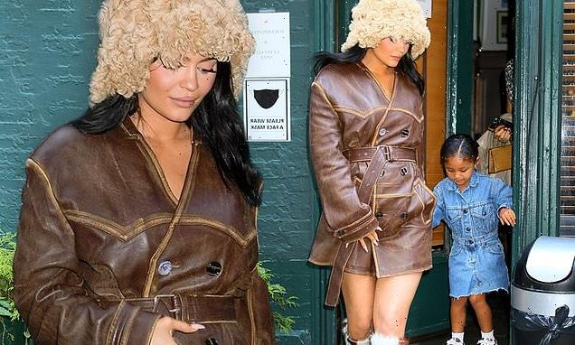 Kylie Jenner places a hand on her baby bump while out with Stormi
